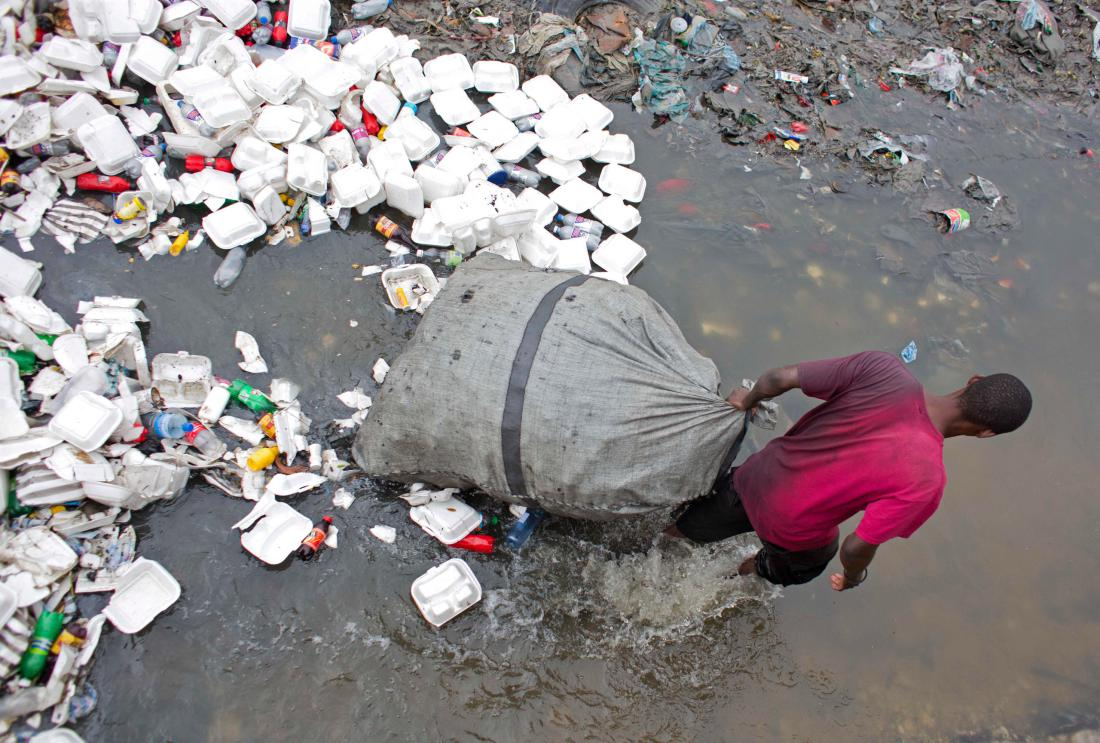 A man wades through a garbage filled water canal in downtown Port-au-Prince, Haiti, on Feb. 28, 2016. Scientists believe cholera was introduced to the country's biggest river by inadequately treated sewage from a base of U.N. peacekeepers. Photo credit: Time